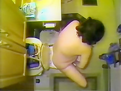 Naked maiden takes a piss in the bathroom