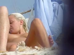 Naked tanned blonde puts her bikini back on