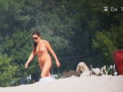 Busty chick caught off guard by a nude beach voyeur