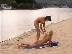 Nude girls outdoor on public beach having fun