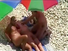 Threesome sex fun on public beach caught on voyeur cam