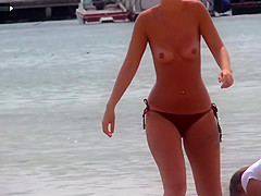 Slim babe with sexy body filmed with her tits out on the beach