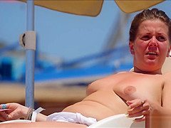 Two babes with natural tits take their bikini tops off on topless beach