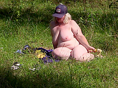 Voyeur in a public place caught a mature milf in the lens, who masturbates outdoors with a banana. Nudist with big tits, fat ass and hairy pussy.