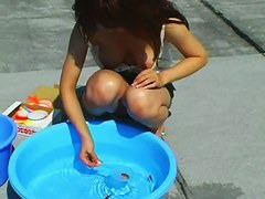 A brunette playing with fishes with her amazing tits hanging out