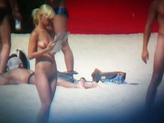 Blonde naked woman on the beach reading a newspaper