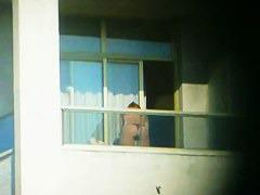 Topless brunette hottie filmed from a window
