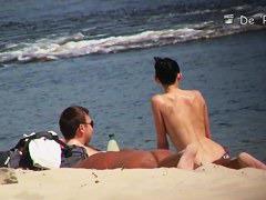 A shy fox with a seductive body stands slim on a beach in a porno