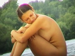 Naked chick on the beach, sitting with her arms over her legs porno