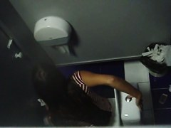 A brunette peeing in the common bathroom